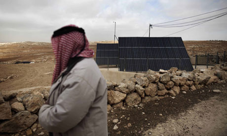 MDG : A Palestinian man looks at a solar panel in the southern West Bank village of Imneizil