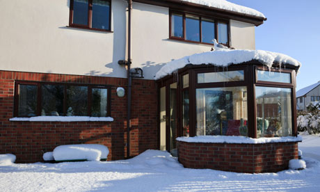 Damian on Green deal : House with conservatory from back garden covered in snow in winter