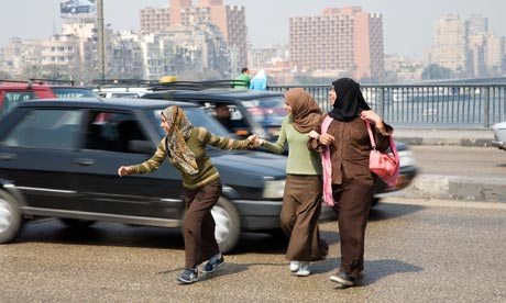 MDG : Road Safety : Pedestrians cross a road durinf  heavy traffic in Cairo, Egypt