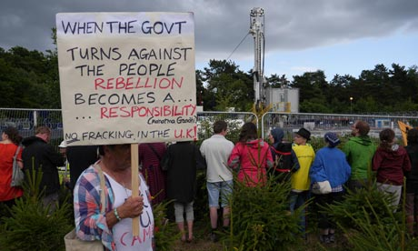 Anti-fracking protest holds a poster with a qote from Ghandi during a protest in Balcombe