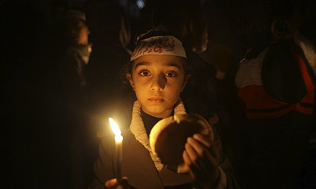 MDG : A Palestinian girl holds a candle during a vigil against the siege of Yarmouk camp, Syria