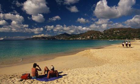 Couple sunbathing on a sandy beach at Grand Anse, Grenada