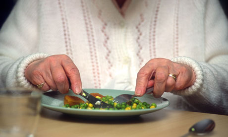 An elderly woman eats her lunch at a day care centre