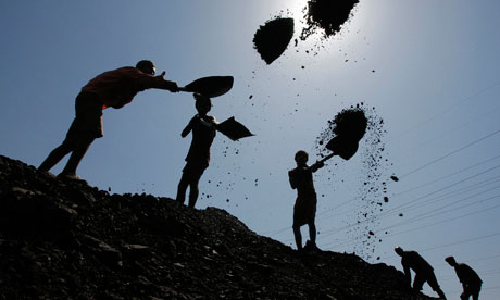 Labourers load coal on trucks at Bari Brahamina in Jammu