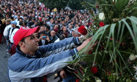 A Tunisian man puts flowers as a tribute