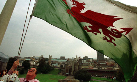 A keeper of Cardiff Castle raises the  Welsh flag over the battlements