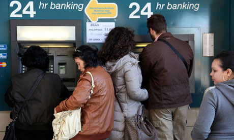 People withdraw money from a cashpoint machine in the Cyprus capital, Nicosia