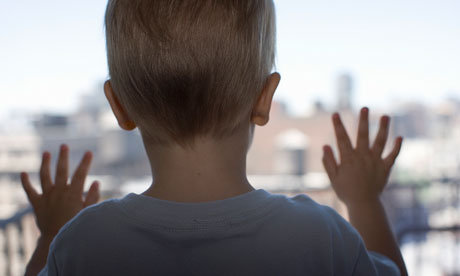 Close up of boy looking out window, rear view