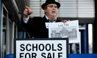 A man dressed as an auctioneer attends a protest staged by the Anti Academies Alliance