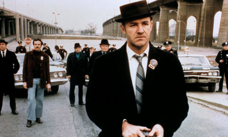 Gene Hackman stands in front of a crowd of police in The French Connection