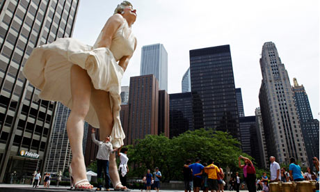 A man jokingly looks under the dress of a 26-foot tall statue of Marilyn Monroe in Chicago
