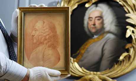 A chalk drawing of Charles Jennens is held in front of a painting of Handel at Handel House Museum.