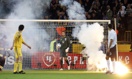 England's David James surrounded by flares thrown by Ukraine fans