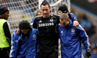 John Terry, centre, is helped off the Stamford Bridge pitch after suffering an achilles injury