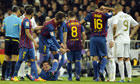 Barcelona's Lionel Messi, centre, gestures in pain following the incident with Real Madrid's Pepe