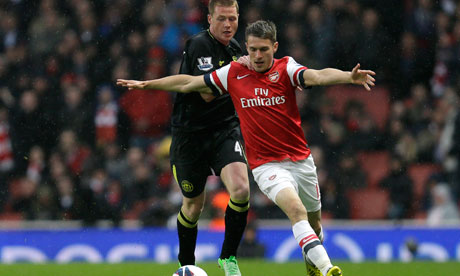 Arsenal's Aaron Ramsey holds off Wigan Athletic's James McCarthy