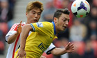 Mesut Ozil, right, is challenged by Sunderland's Ki Sung-Yeung during Arsenal's 3-1 victory