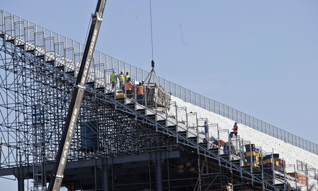 Construction workers focus on a stand at the Arena Corinthians stadium in São Paulo, Brazil