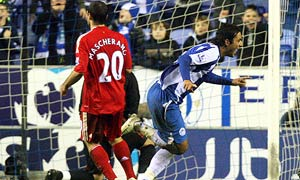 Wigan Athletic's Mido, right, celebrates his goal, as Liverpool's  Javier Mascherano, left, looks on