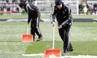 Groundstaff sweep snow off the pitch