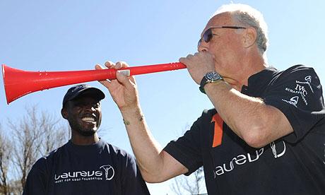 Franz Beckenbauer blows a vuvuzela horn