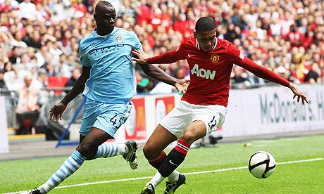 Manchester City's Mario Balotelli and Manchester United's Chris Smalling contest the ball