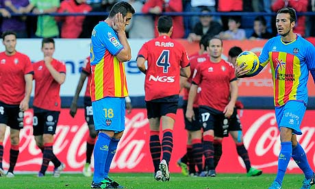 Levante's Sergio Ballesteros, left, reacts after Osasuna scored during their victory