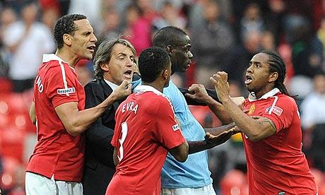 Manchester City manager Roberto Mancini holds back Mario Balotelli