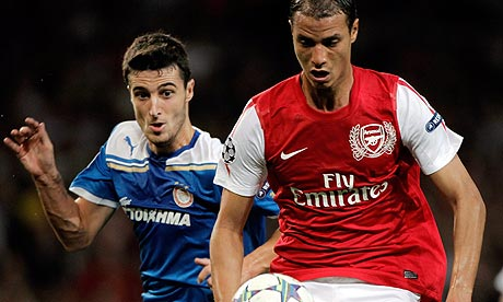 Arsenal's Marouane Chamakh shields the ball from the Olympiakos player Francois Modesto