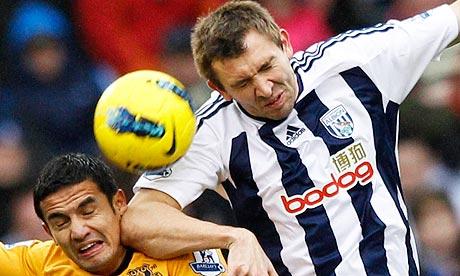 Gareth McAuley challenges Tim Cahill