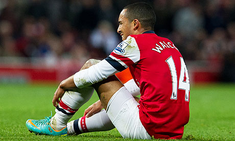 Arsenal's Theo Walcott sits on the pitch shortly before being substituted against Fulham