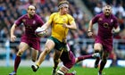 Michael Hooper, centre, of Australia breaks with the ball against England