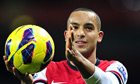 Theo Walcott applauds the crowd after claiming the match ball