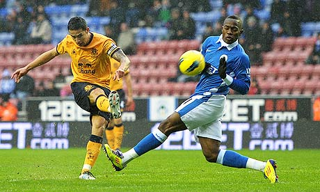 Everton's Tim Cahill, left, has a shot at goal near Wigan Athletic's Maynor Figueroa