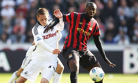 Swansea City's Gylfi Sigurdsson tussles with Manchester City midfielder Yaya Toure