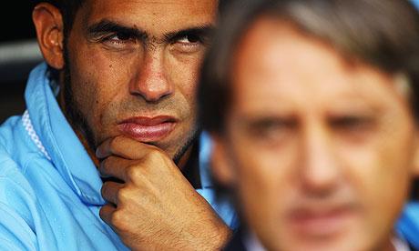 Carlos Tevez sits behind Roberto Mancini