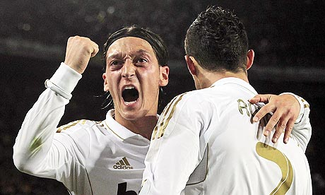 Real Madrid's Mesut Ozil, left, congratulates Cristiano Ronaldo on his winning goal at Barcelona