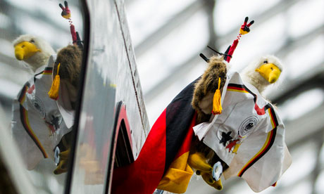 A man waves a mascot version of the German Federal Eagle as he leaves Berlin's main train station