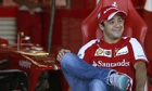 Ferrari Formula One driver Massa of Brazil smiles in the garage at the Suzuka circuit
