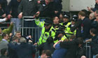 Police officers wield batons as they attempt to stop Millwall supporters fighting amongst themselves