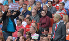 A fan holds a protest banner as Arsène Wenger watches Arsenal's 3-1 defeat to Aston Villa