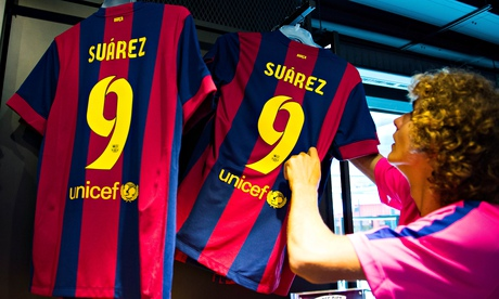 An employee hangs shirts of new Barcelona player Luis Suárez at the club's official store
