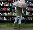 A woman looks at outdoor book shelves in the rain at The Guardian Hay Festival 2008
