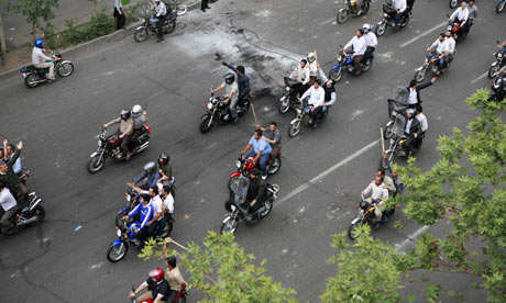 Iranians armed with batons ride on motorcycles during protests in central Tehran
