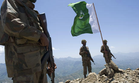 Pakistani soldiers stand guard on top of a mountain overlooking the Swat valley