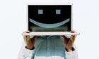 Man holding up laptop displaying smiley face