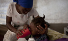 A woman takes care of her daughter, who is suffering from cholera in Cite Soleil, Port au Prince