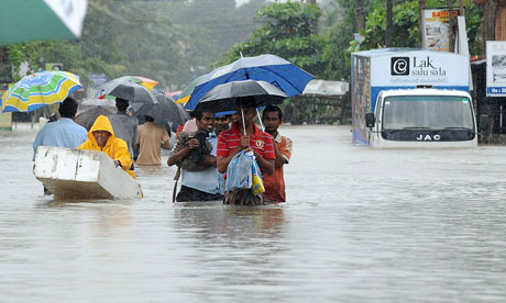 Residents walk along a flooded road in P