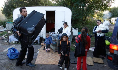 A Roma family leave a camp