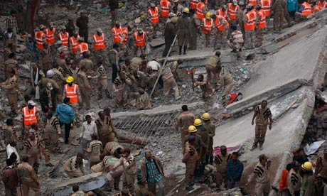 Indian rescue workers search the debris of a collapsed tenement in New Delhi